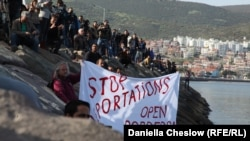 Акция протеста в день прибытия первого парома с мигрантами в Турцию. Протестующий держит плакат с требованием прекратить депортацию и открыть границы. Дикили, 4 апреля 2016 года.