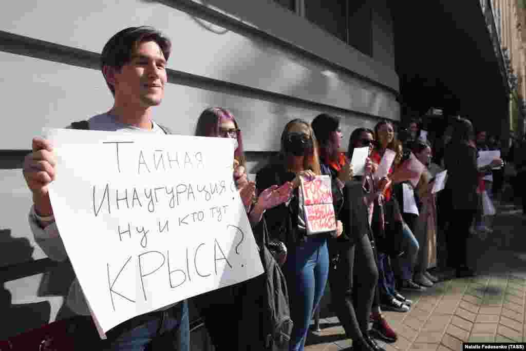 На фото: хлопець тримає плакат із написом:«Таємна інавгуація? Ну, і хто тут щур?»