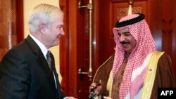 U.S. Defense Secretary Robert Gates (left) presents a bronze eagle statue to Hamad bin Isa Al Khalifa, king of Bahrain, during a visit to Safryia Palace.