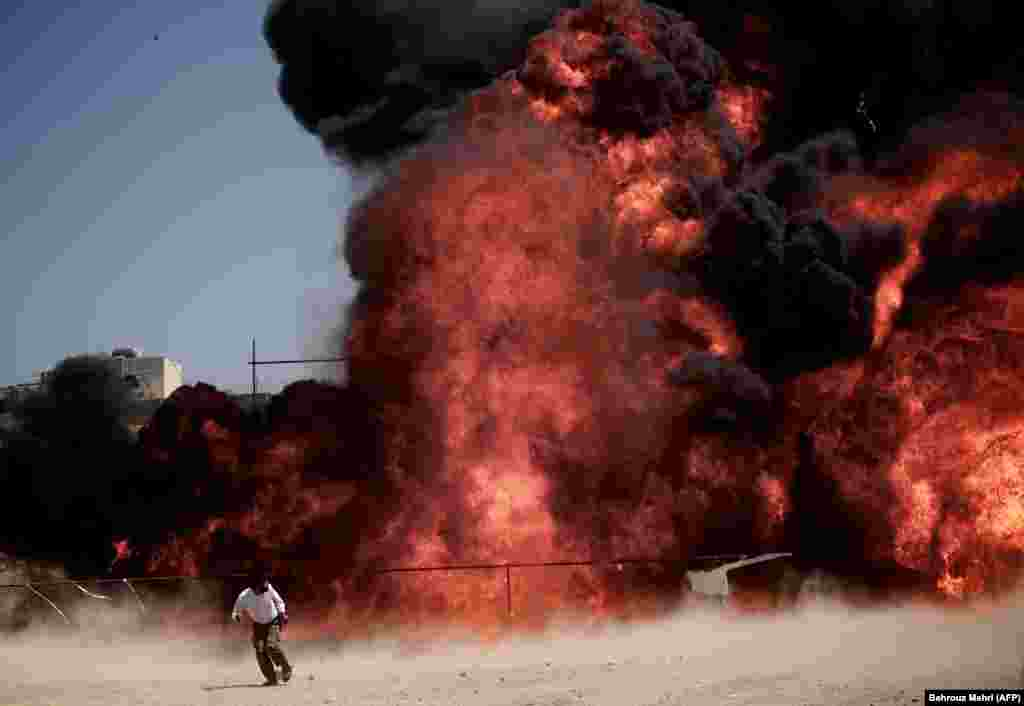 A man who was fixing explosives wires run away after setting ablaze 50 tons of drugs seized in recent months in eastern Tehran. (AFP/Behrouz Mehri)
