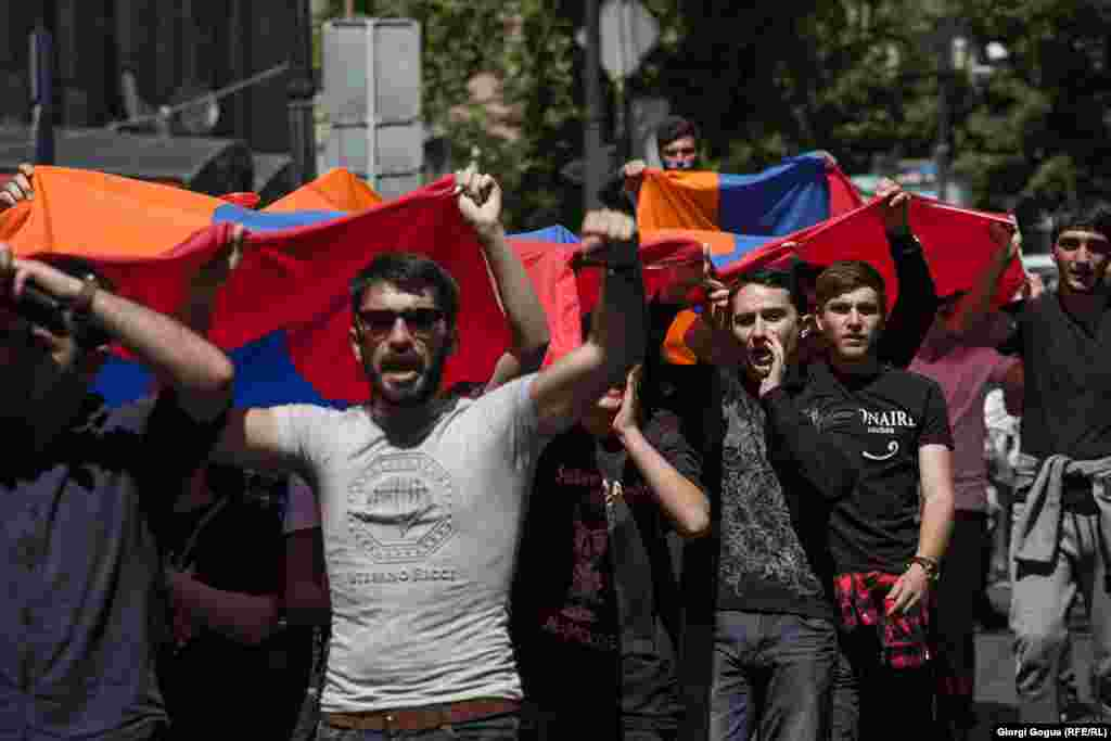 Young supporters of protest leader Nikol Pashinian march with the Armenian flag.