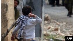 Fələstinli uşaq İsrail təhlükəsizlik qüvvələrinə daş atır.
