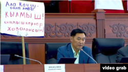 Жогорку Кеңештин депутаты Эмил Токтошев парламент жыйынына алып кирген плакат. 8-апрель, 2021-жыл.