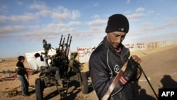 Rebel fighters man their antiaircraft guns in the town of Ras Lanouf today, as Libyan state television claimed that the city had been recaptured by loyalist forces.