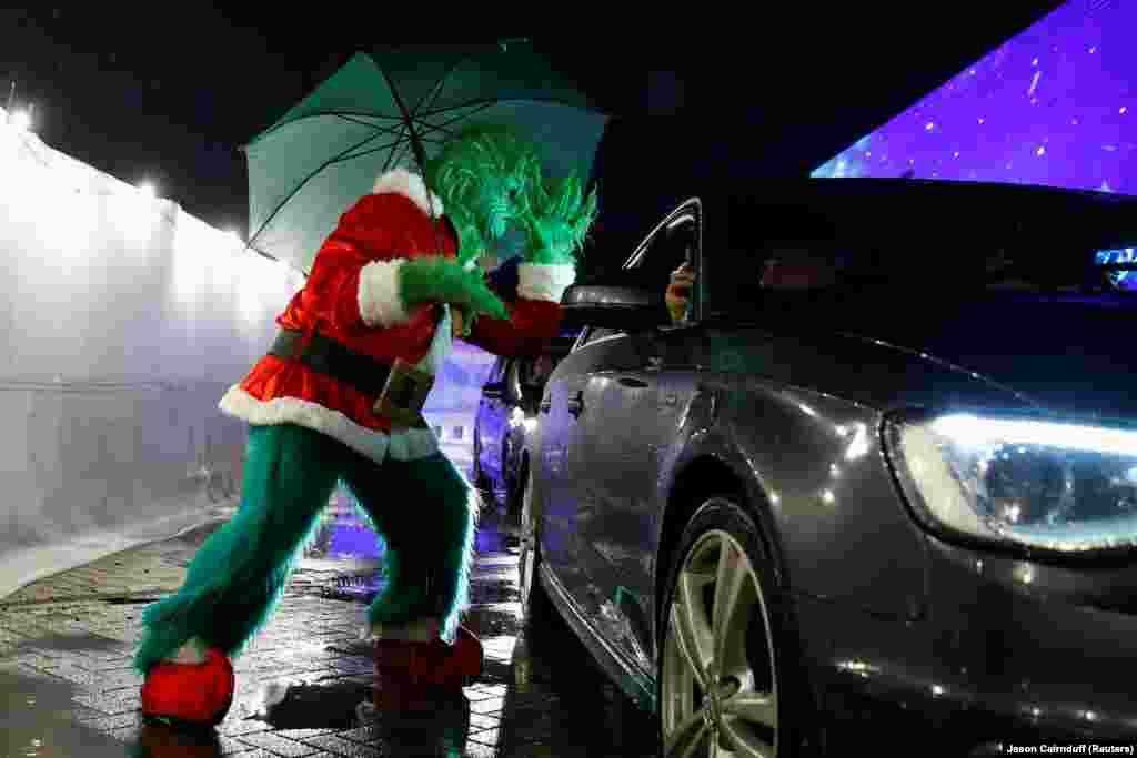 Особа, одягнена в костюм Ґрінча, під час виступу, коли люди відвідують показ фільму «Один вдома» в кінотеатрі «Різдвяне місто» у Манчестері, Велика Британія, 3 грудня 2020 року