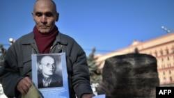 Мужчина держит фотографию репрессированного при Сталине человека на акции памяти у Соловецкого камня. Москва, 29 октября 2014 года.