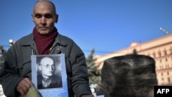 A man holds his father's portrait near a memorial to the victims of Soviet-era political repressions on Lubyanka Square in Moscow on October 29.