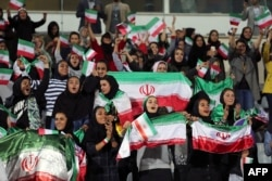 Iranian women cheer during the friendly between Iran and Bolivia at Azadi Stadium in Tehran on October 16.