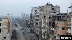 Damaged buildings line a street in the besieged area of Homs.