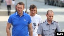Алексей Навальный в сопровождении полицейского прибывает на слушания