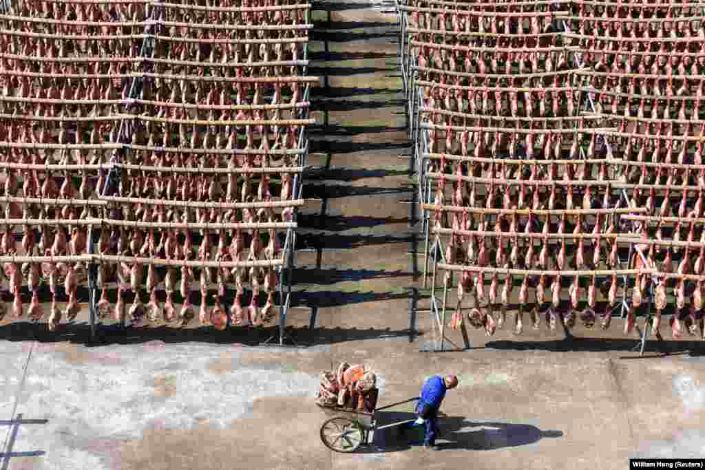 A worker pulls a cart filled with Jinhua ham at a processing facility in China's Zhejiang Province. (Reuters/William Hong)
