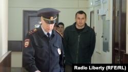 Украинский режиссер Олег Сенцов (справа) в сопровождении полицейских.