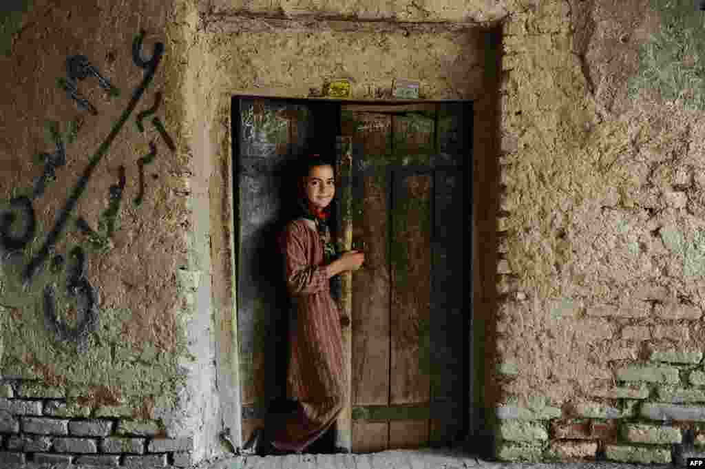 A girl stands in the doorway of her house in the old sector of Herat, Afghanistan. (AFP/Aref Karimi)