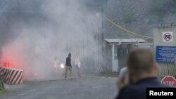 Poliţist kosovar, urmărind devastarea punctului de trecere de la Jarinje, la frontiera cu Serbia, 27 iulie 2011