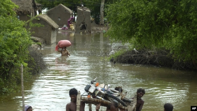 Pakistani villagers carry a motorbike as they flee their flooded homes in Badin in Sindh Province.