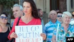 """Boeing 777 ұшағы жолаушыларының қазасына қатысты Харьковтегі қаралы жиынға келген әйел """"Путин Гаага сотына тартылсын"""" деген плакат ұстап тұр."""