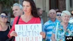 """Участница траурной церемонии в Харькове, куда были доставлены тела пассажиров """"Боинга"""", держит плакат с призывом судить Владимира Путина в Гааге."""