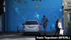 Көліктің астын арнайы айнамен тексеріп жатқан күзетші. Алматы, 4 қазан 2016 жыл.