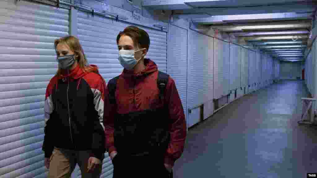 Девушка и юноша идут вдоль закрытых торговых киосков в подземном переходе на площади Советской в Симферополе