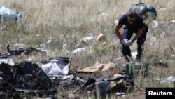 A member of a group of international experts inspecting the site where the downed Malaysia Airlines Flight 17 crashed, near the village of Hrabove in the Donetsk region of eastern Ukraine, in mid-July.