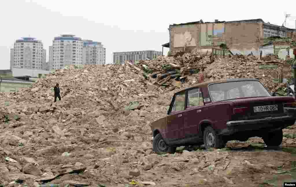 A man walks on the rubble of demolished houses in Baku. Entire districts were razed in the development of new landmarks in the city of 2 million.