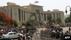 Müsüriň howpsuzlyk güýçleri Ýokary Konstitusion suduň binasyny protestçilerden goraýar. Kair, 14-nji iýun, 2012.