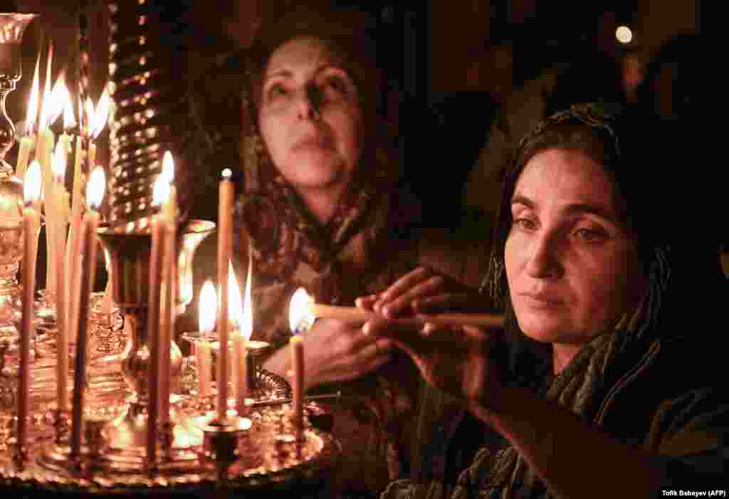 Women light candles during an Orthodox Easter Sunday service in a church in Baku, Azerbaijan, on April 8. (AFP/Tofik Babayev)