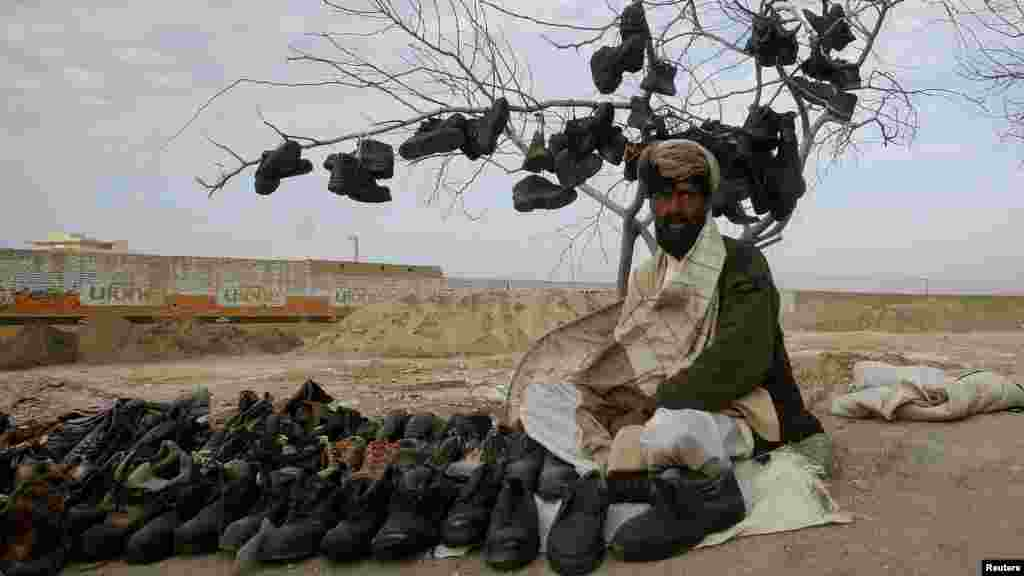 A man waits for customers while selling used shoes at his roadside stall in Quetta, Pakistan, on March 2. (Reuters/Naseer Ahmed)