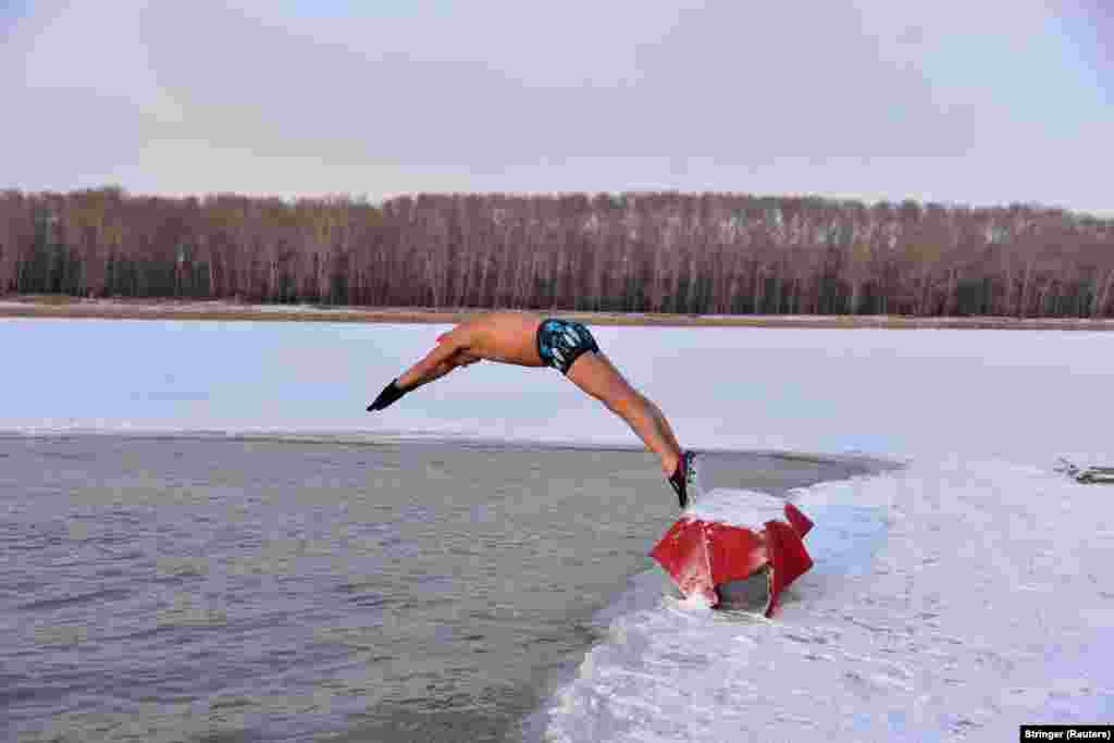 A winter swimmer dives into the icy water of the Songhua River in Songyuan, Jilin Province, China. (Reuters/Stringer)