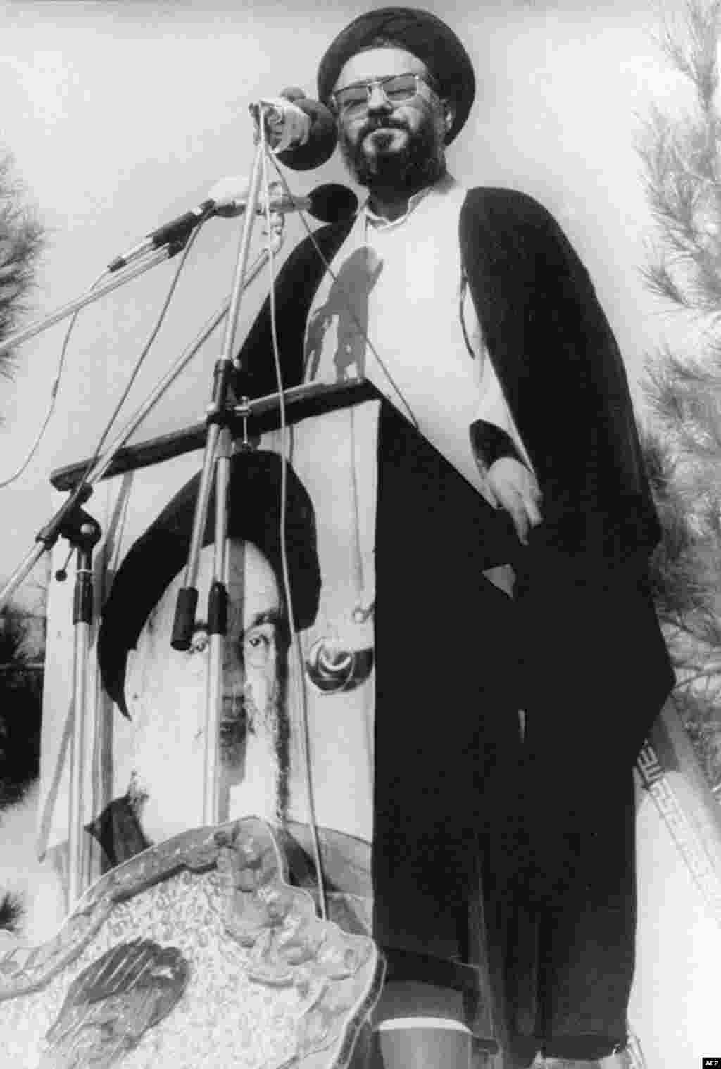 Student leader Ayatollah Musavi Khoeniha speaks from the top of a U.S. Embassy wall on the siege's first anniversary.