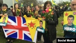 """Members of Britain's Kurdish community wait at Manchester Airport on March 20 for Konstandinos """"Kosta"""" Erik Scurfield, a British man who died fighting the Islamic State (IS) group in Syria."""