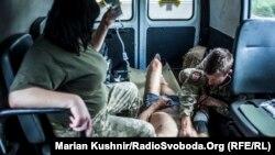 Медики надають першу допомогу пораненому уламками міни жителю Авдіївки