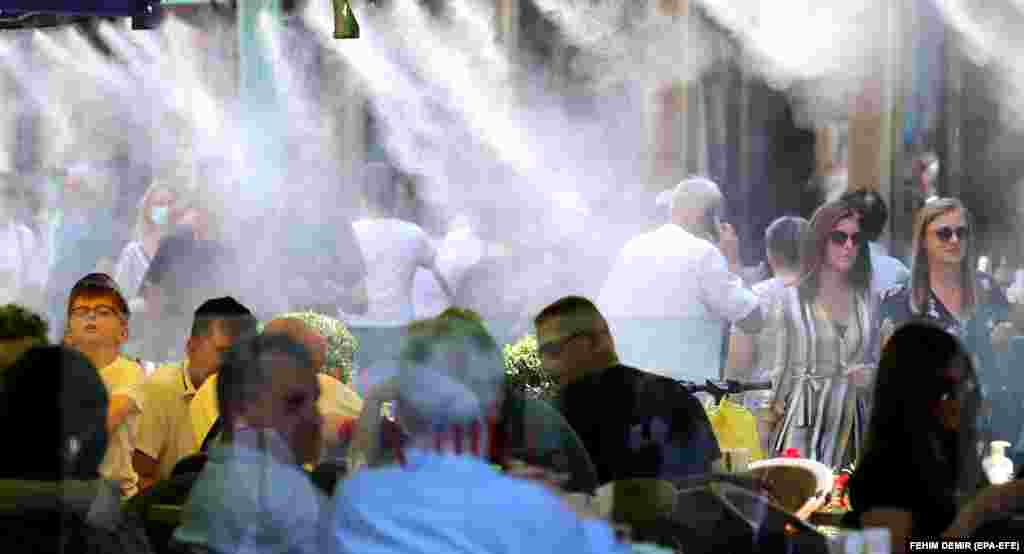 Water sprinklers cool guests in a cafe and people on the main street in Sarajevo, as temperatures in the Bosnian capital reached almost 30 degrees Celsius on July 6.