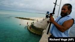 Kiribatin, a Tarawa-atoll hídján horgászik egy férfi 2004. március 30-án.
