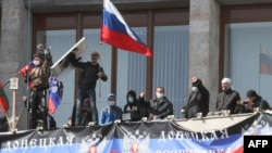 Pro-Russian activists who seized the main administration building in Donetsk wave a flag of the so-called Donetsk Republic and hold a Russian flag on April 7.