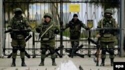 Bărbați înarmați păzesc o unitate militară ucraineană din satul Perevalnoie, lîngă Simferopol,19 martie 2014