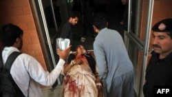 Pakistani volunteers move a man injured in a bomb attack into a hospital in Peshawar following a suicide bomb attack on a government building in Mardan on April 19.