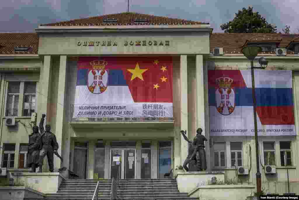 """Un banner care leagă drapelele Serbiei și Chinei și cele sârbe și ruse pe o clădire municipală din sudul Belgradului, pe 13 aprilie. Mesajuldin stânga, în litere chirilice: """"Prieteni de fier, împreună la bine și la rău!"""" și, în dreapta: """"Mulțumesc Rusiei Surori! Mulțumesc Fraților ruși! """""""