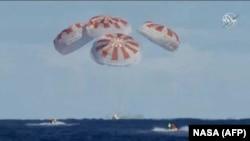 Капсула Dragon приводняется после первого успешного испытательного полета с манекеном на борту 8 марта 2019 года.
