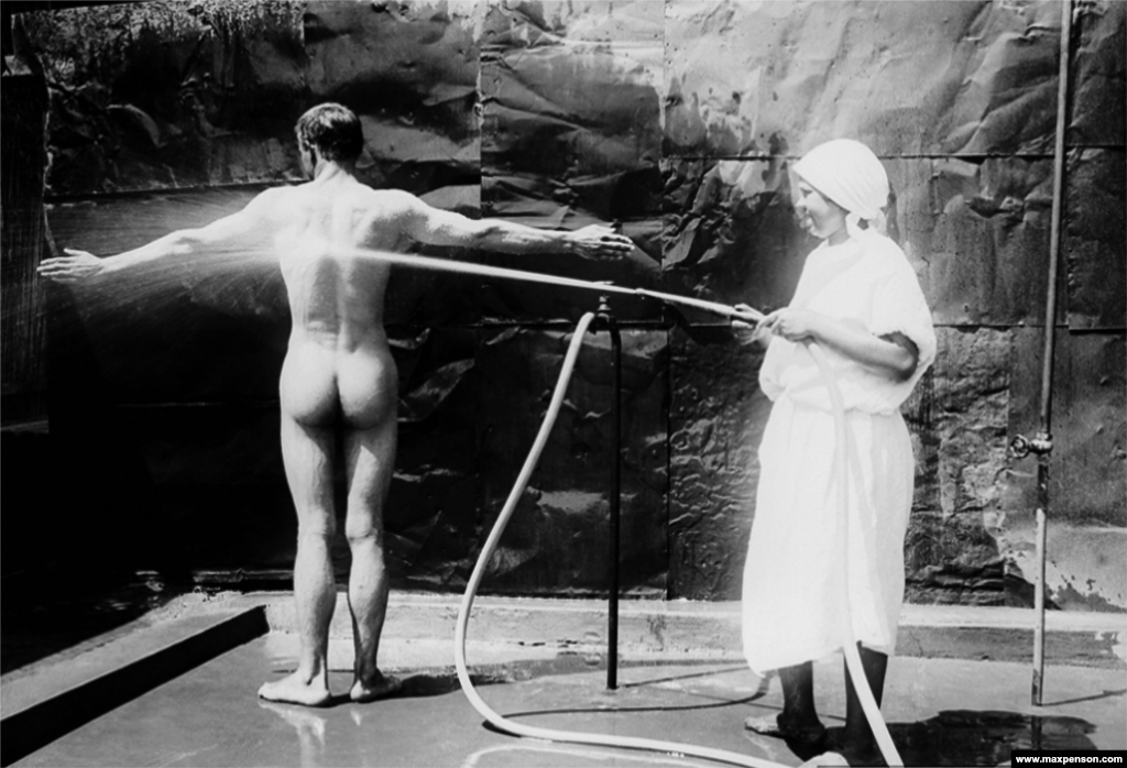 A nurse hoses down a patient in a photograph titled In The Hospital.