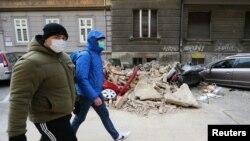 Люди проходят мимо поврежденных землетрясением автомобилей. Загреб, Хорватия,, 22 марта 2020 года.