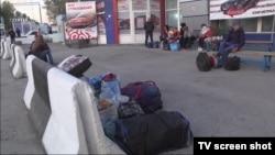 """Люди с сумками ожидают у таможенного поста """"Кордай"""" с казахстанской стороны границы. 11 октября 2017 года."""
