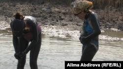 Девушки мажут на себя лечебную грязь на озере Батпакты Алгинского района Актюбинской области. 10 августа 2010 года.