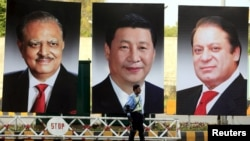 A policeman stands guard next to giant portraits of Pakistani President Mamnoon Hussain, Chinese President Xi Jinping, and Pakistani Prime Minister Nawaz Sharif ahead of Xi's visit to Islamabad.