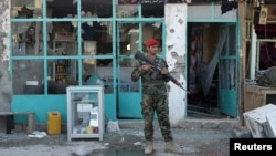 Afghan National Army (ANA) soldiers stand guard in front of a shop burned during the Taliban attack on Kandahar Airport in Kandahar on December 9.