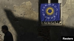 Georgia -- A pedestrian walks past a window decorated with the Georgian Dream coalition flag in Tbilisi, 03Oct2012