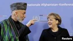 German Chancellor Angela Merkel (right) talks with Karzai in Bonn on December 5.
