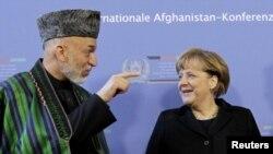 German Chancellor Angela Merkel (right) talks with Karzai in Bonn on December 5.