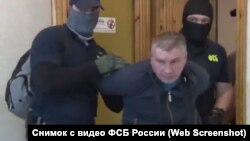 FSB officers arrest Russian serviceman Dmitry Dolgopolov (center) on suspicion of spying for Ukraine.