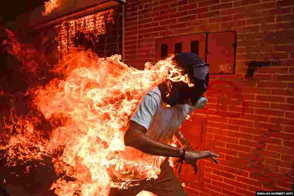 """""""Фото года"""" На снимке – 28-летнийХосе Виктор Салазар Бальза, охваченный огнем.3 мая 2017 года он участвовалв акции протеста против президента Венесуэлы Николаса Мадуры и пострадал в столкновениях с полицией."""